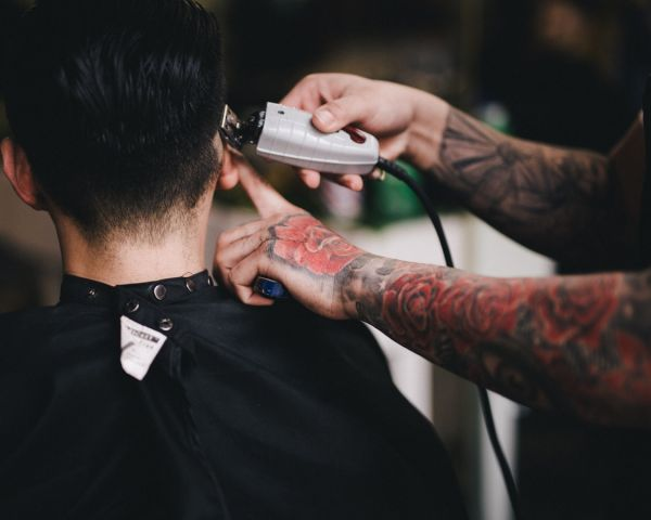 Barber using clippers to cut short hair