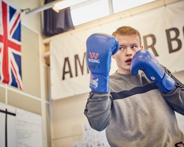 Young man with blue boxing gloves