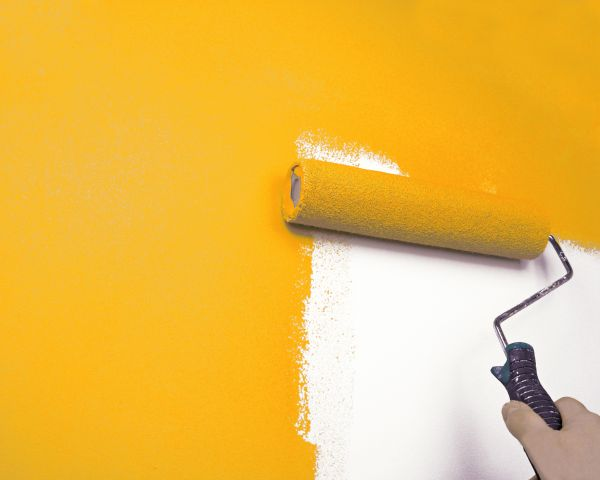 Paint roller painting a wall yellow