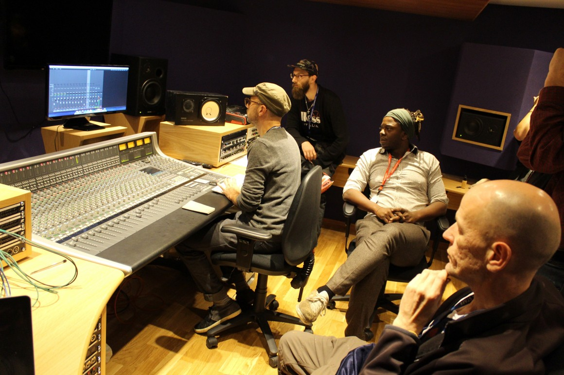 A group of staff and students in a recording studio with recording equipment and a computer screen in front of them